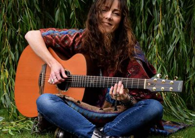 carrie-martin-plays-guitar-under-willow-tree-smiling